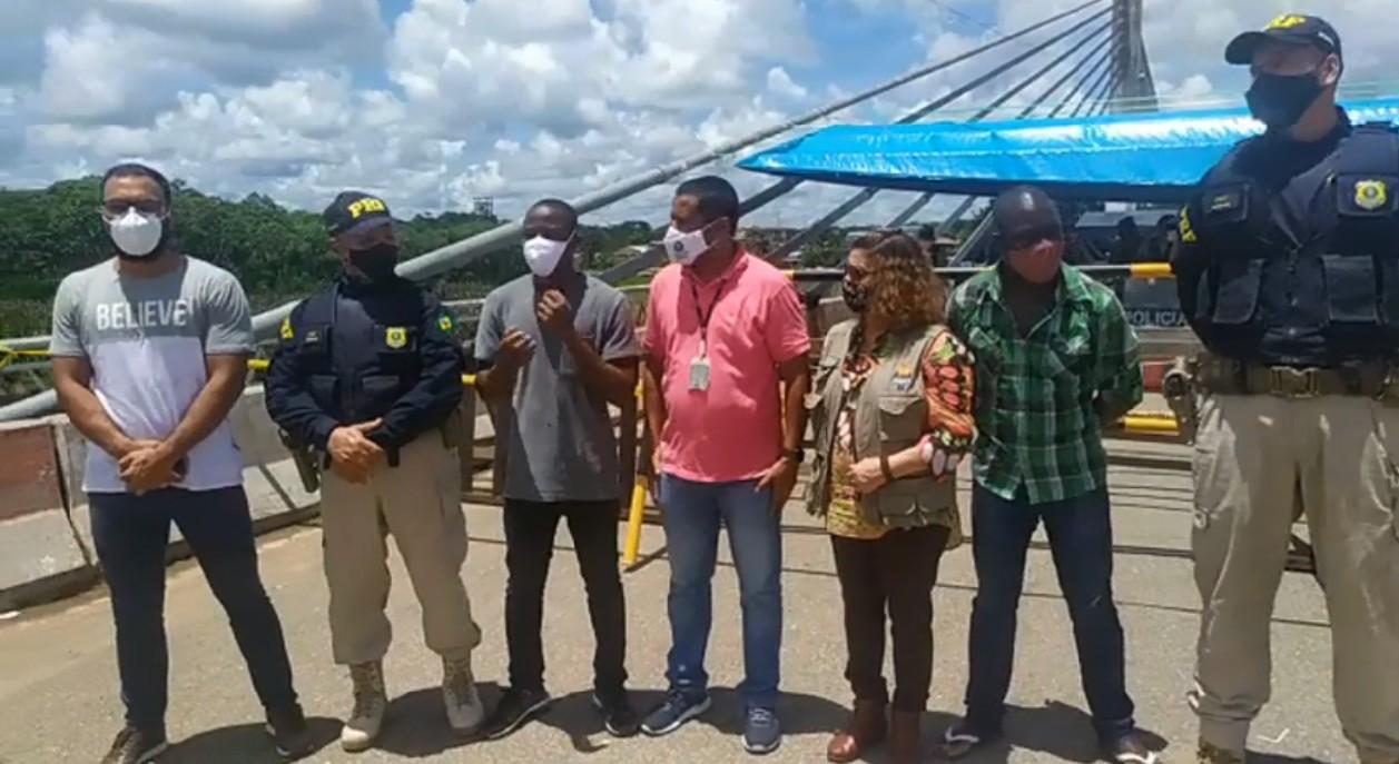 Imigrantes e autoridades brasileiras durante ato de desocupação da ponte que liga o Brasil ao Peru, no Acre