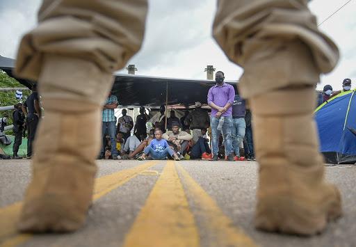 Policiais peruanos bloqueiam ponte que liga o Peru ao Brasil, na qual imigrantes acampam em protesto