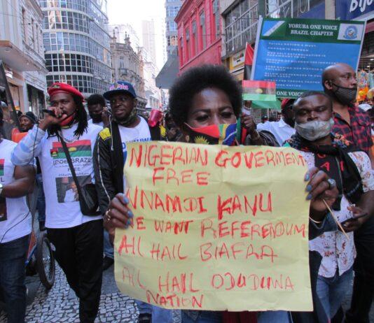 Ativistas nigerianos caminham pelas ruas do centro de São Paulo durante ato.