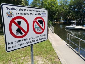 This image on Walker on the Water depicts a sign that warns visitors against dumping scallop shells in Crystal River.