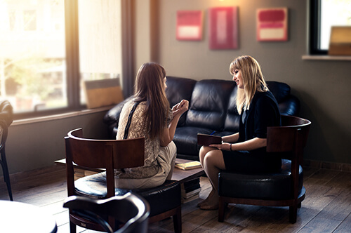 psychologist consulting a woman client indoors discussion therapy