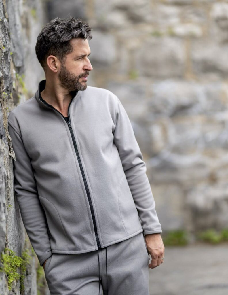 Male model wears a gray tracksuite while leaning against a stone wall
