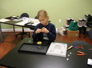 A young girl works on beading a necklace at a class offered by The Twisted Bead & Rock Shop.