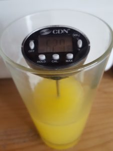 Food thermometer in orange juice checking that it is cold.