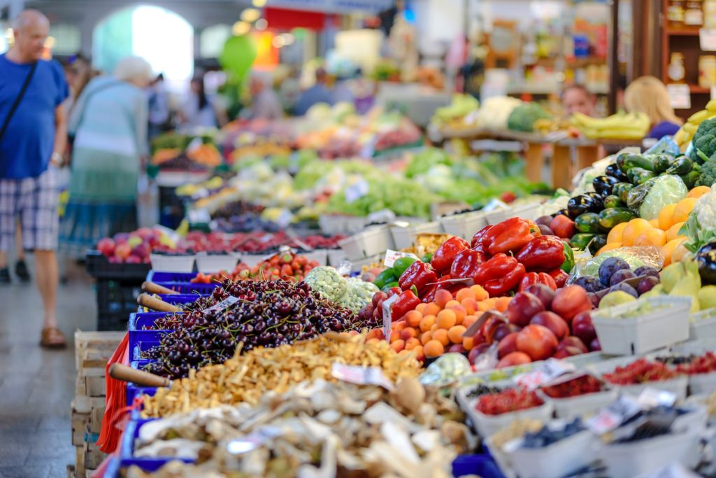 A view of a market stall with lots of colorful fruit and vegetables.