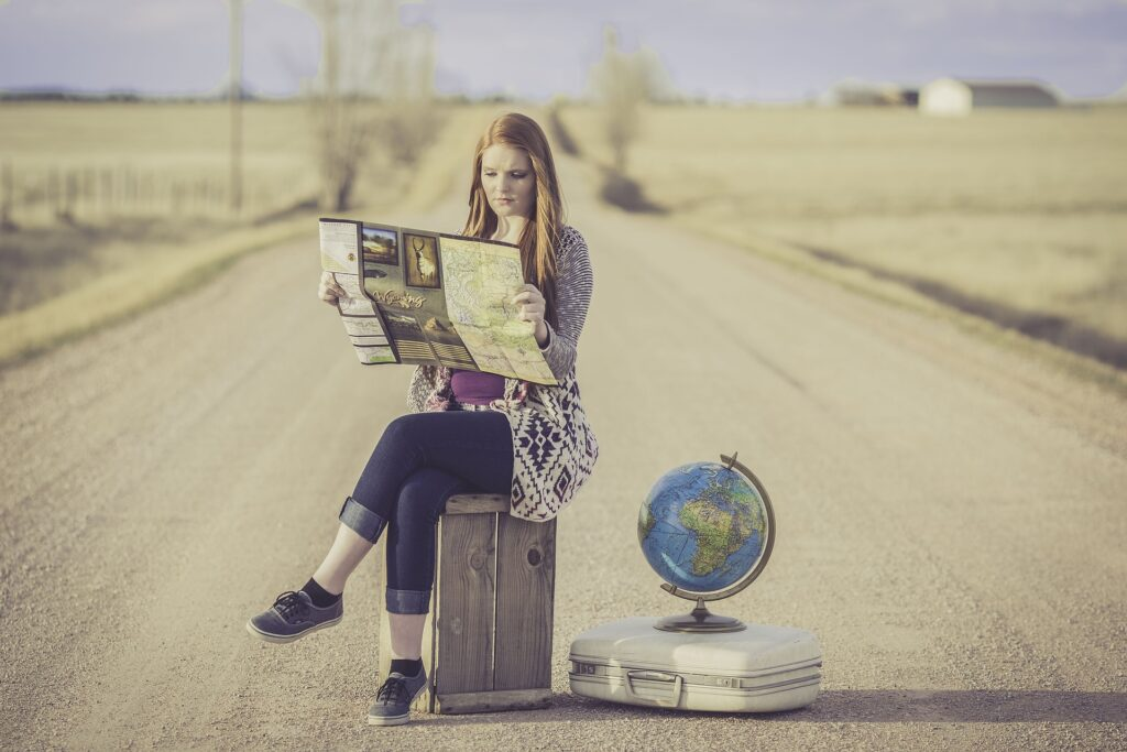 A woman in the middle of a roadsitting on a box next to globe on a suitcase. She is reading a map; obviously planning the future.