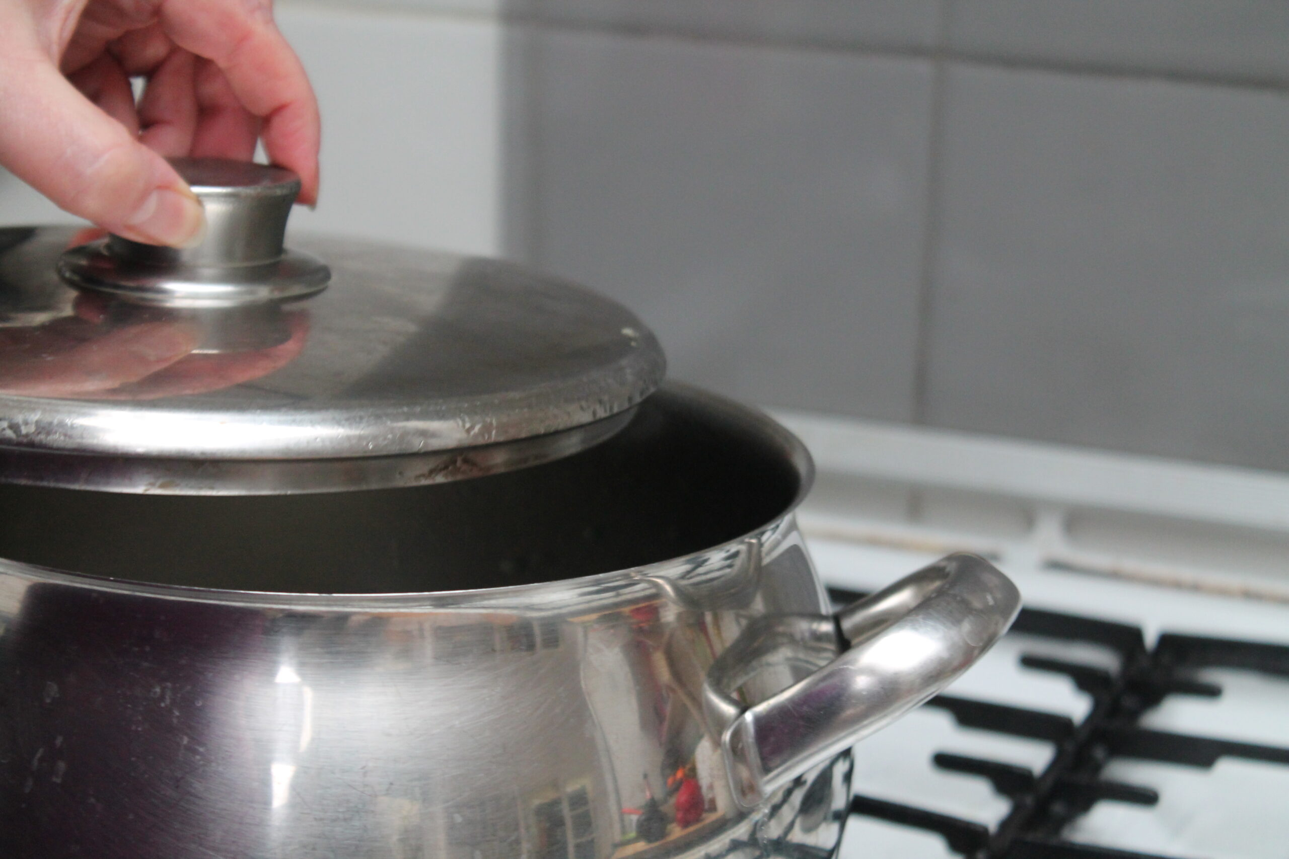 Pan on stove with lid being opened. What is inside? Is the food being cooked properly?