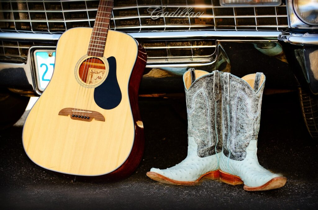 A guitar and a pair of cowboy boots representing country music.