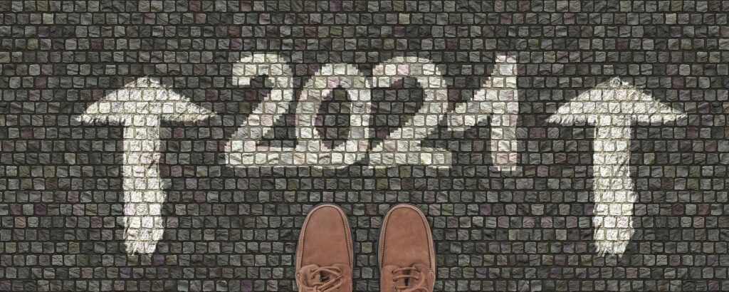 2021 written on paving with two arrows facing forward. Two shoes are lined up ready to enter into 2021.
