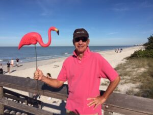 author posing with a plastic flamingo on a FL beach