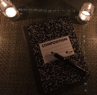 An old-fashioned composition book lit by candlelight to convey the idea of a writer searching to begin a book