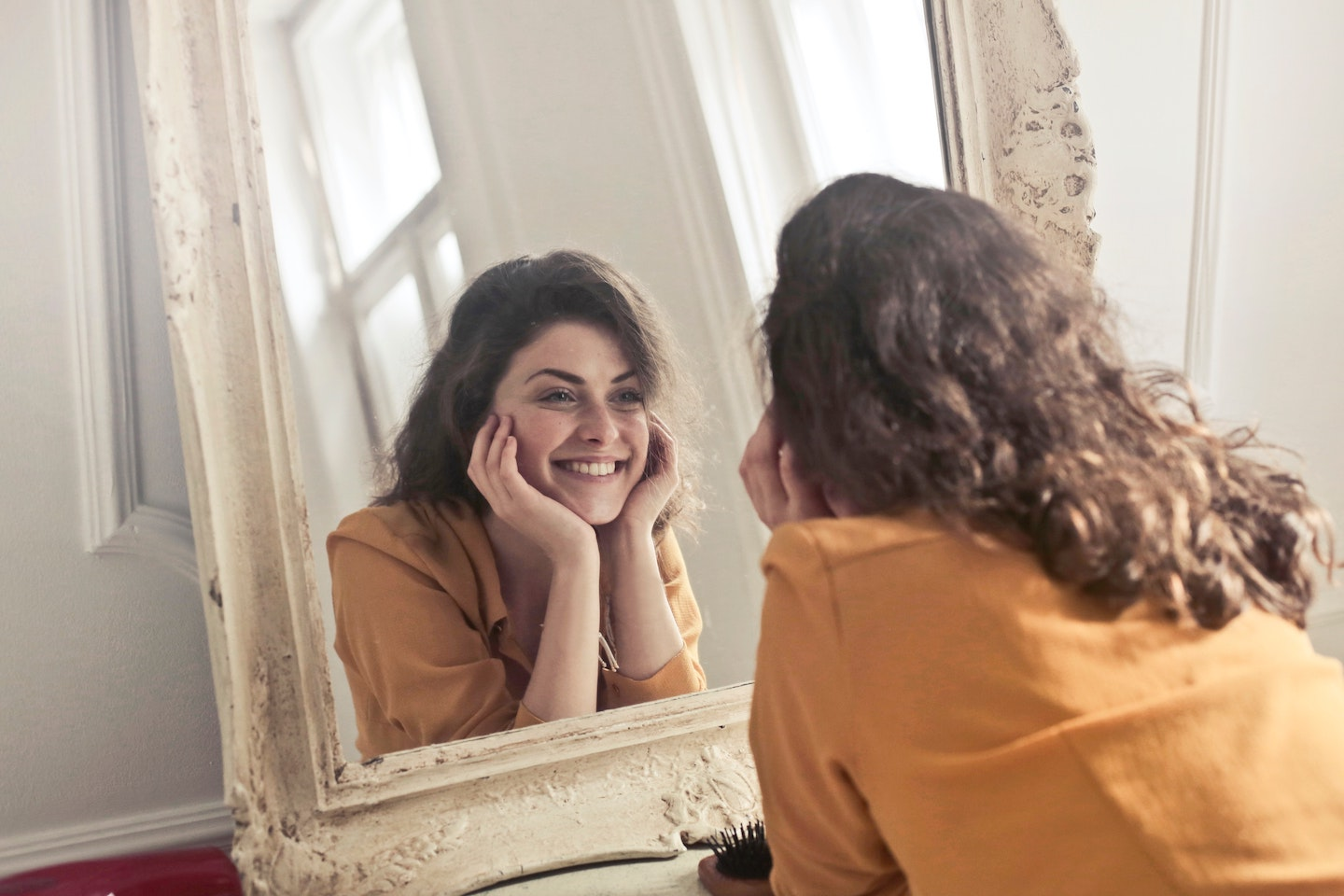 girl-smiling-looking-into-mirror