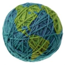 A ball of yarn made to look like the earth, isolated on a white background, with shallow focus on the front of the ball.