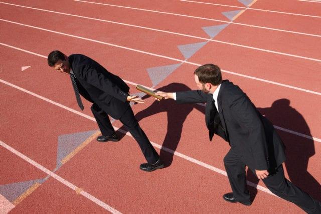 Businessmen passing the baton