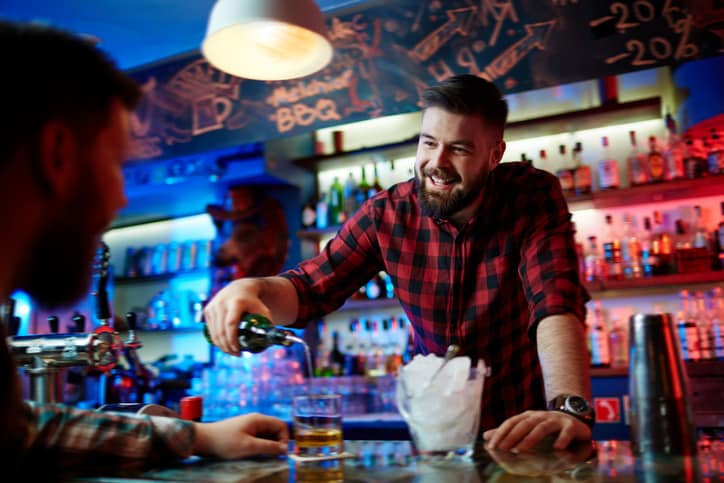 Man pours liquor for customer at a bar