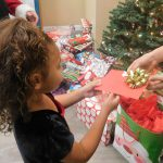 young girl receiving gift at Christmas dinner