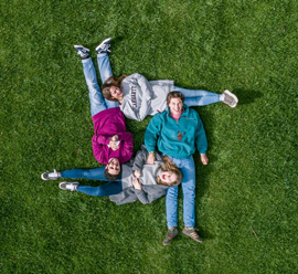 family laying on the green grass shot from birds eye view