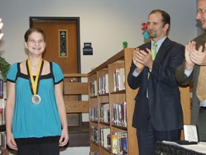 Courtney Fedeson is applauded by the Rockford Board of Education and guests for her community volunteer efforts. She earned $1,000 and a trip to Washington, D.C. when she earned one of the state of Michigan's two top student volunteer awards.