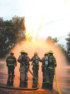 WALL OF WATER—Firefighters practiced this formation, which allows the center person to reach through a protective wall of water into the flames. If this technique is not done correctly, propane and flame escape under the water and burns around rescue workers' legs and lower bodies. Firefighters practiced putting out home propane units, meter fires and grill propane fires.