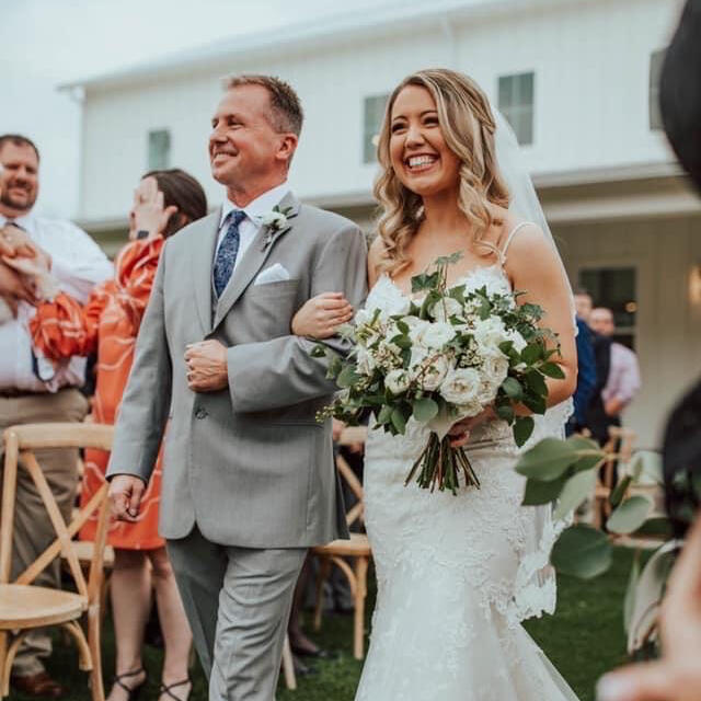 bride wearing lace wedding dress walking down the isle with her dad in texas