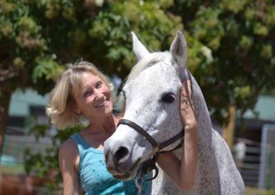 Woman with arm around horse