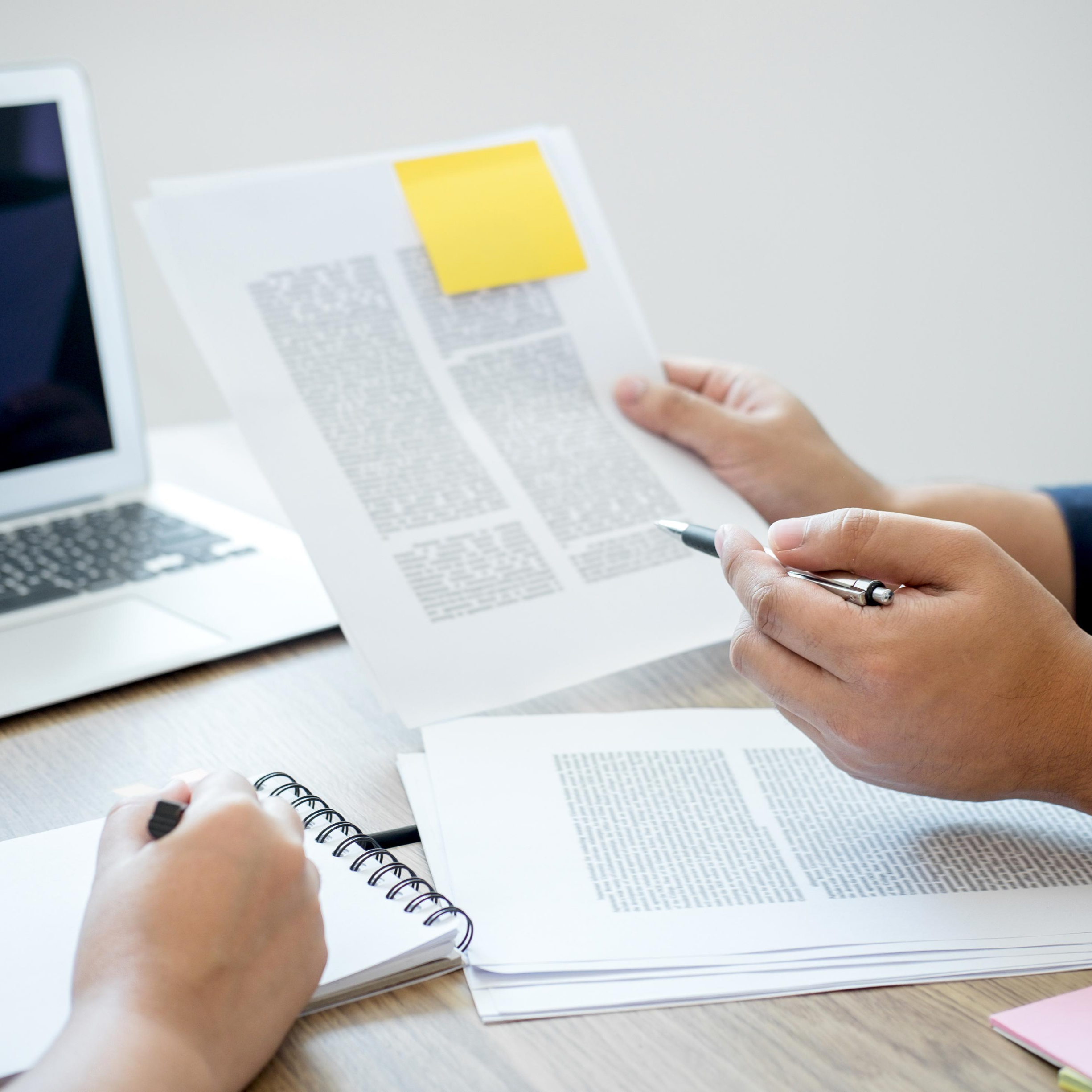 """Open computer in background with two individuals at wooden desk with one writing on notebook with one holding paper with pen and yellow sticky note on paper, represents """"Find A Tutor"""" program"""