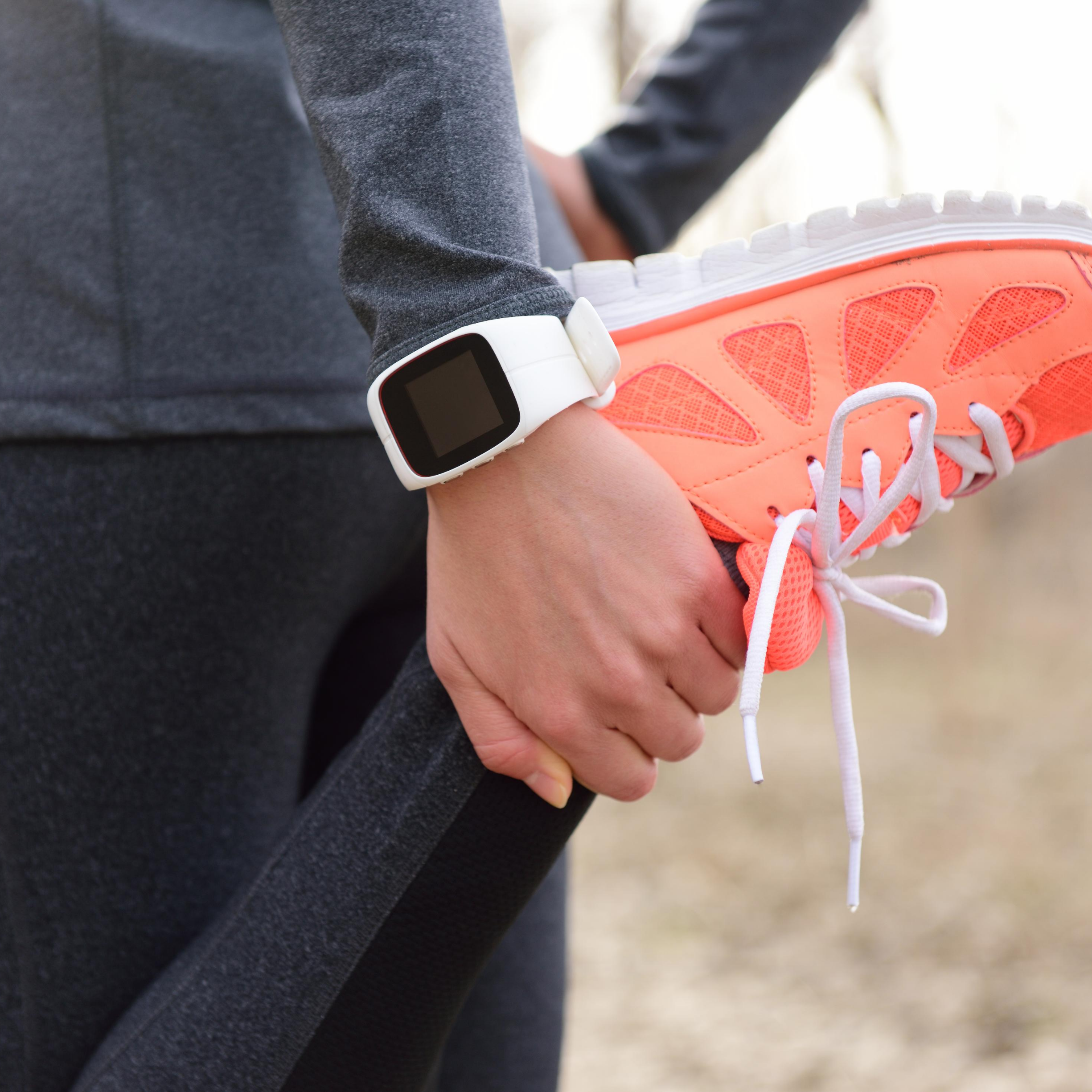 """Individual Stretching front of leg with grey long sleeve top, black leggings, white watch and coral sneakers, represents """"Feeling Sluggish, 30 Min Class to Jumpstart Your System"""" program"""
