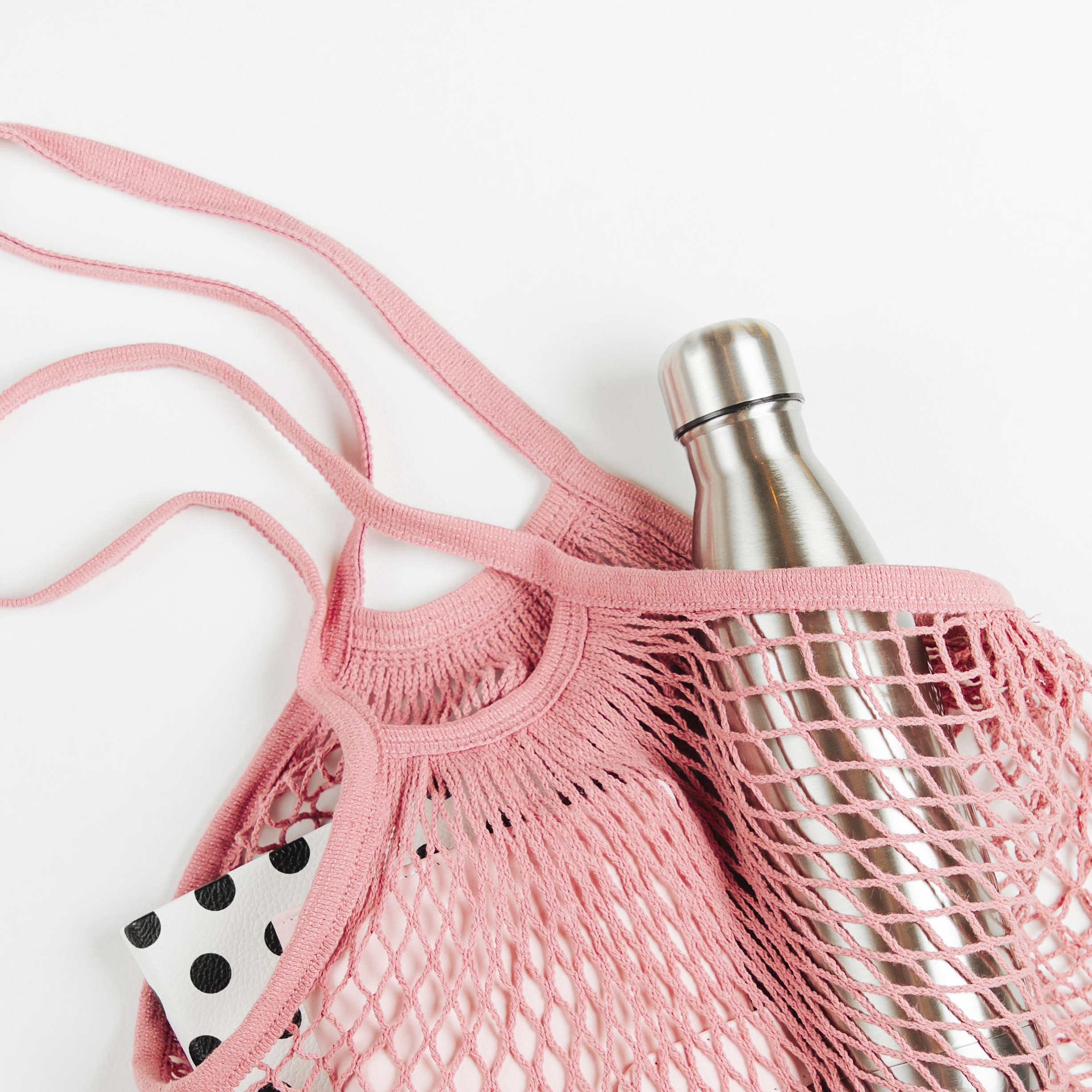 """Stainless steel water bottle in pink mesh tote bag on white background, represents """"Log Your Water Intake"""" program"""