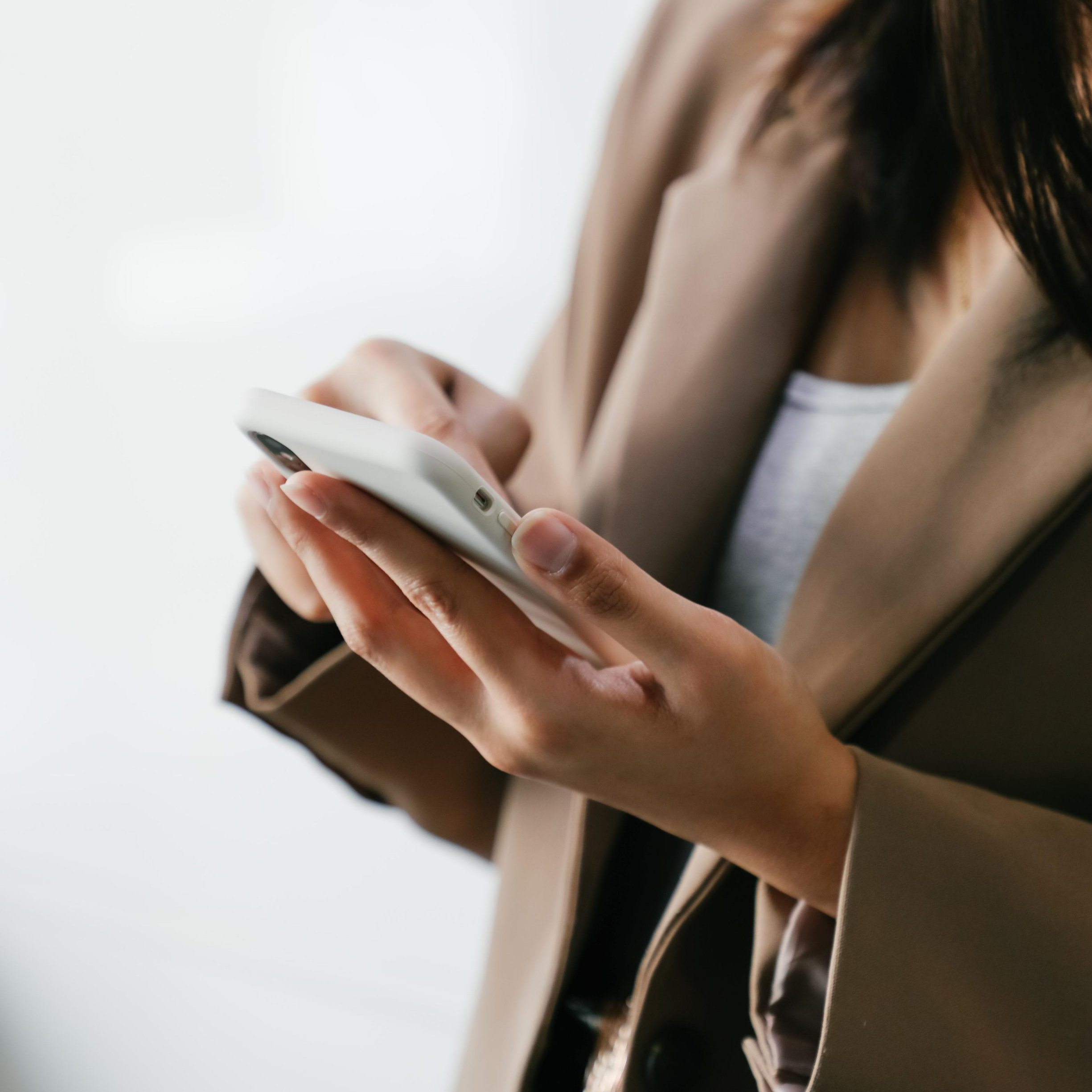"""Woman in brown blazer typing on white iphone with brown hair, represents """"Assess Your Unique Selling Proposition"""" program"""