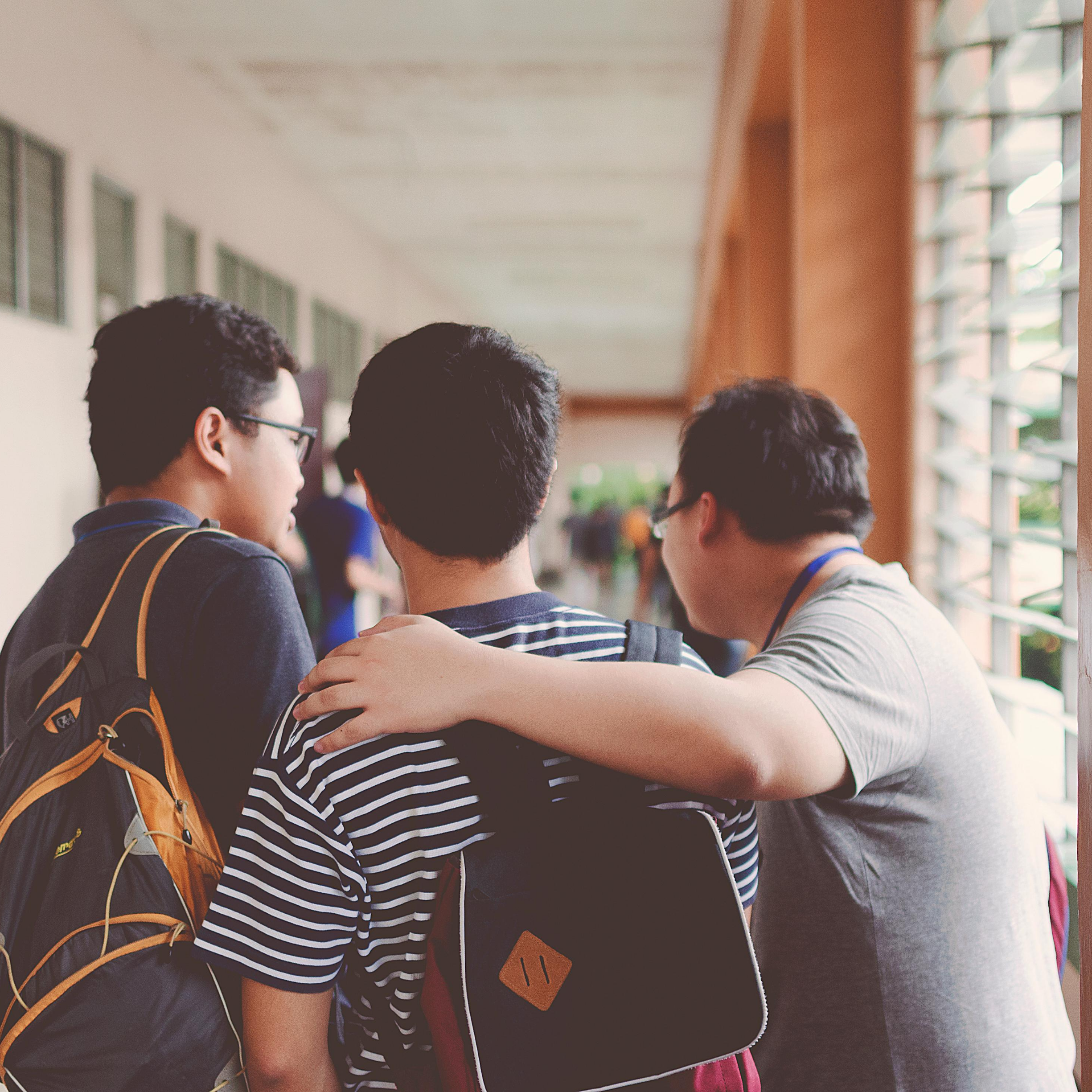 """Three men walking in hallway with backs towards screens, two with back packs, one in striped shirt, one in grey shirt and one in navy shirt, represents """"Connect with Your Peers"""" program"""
