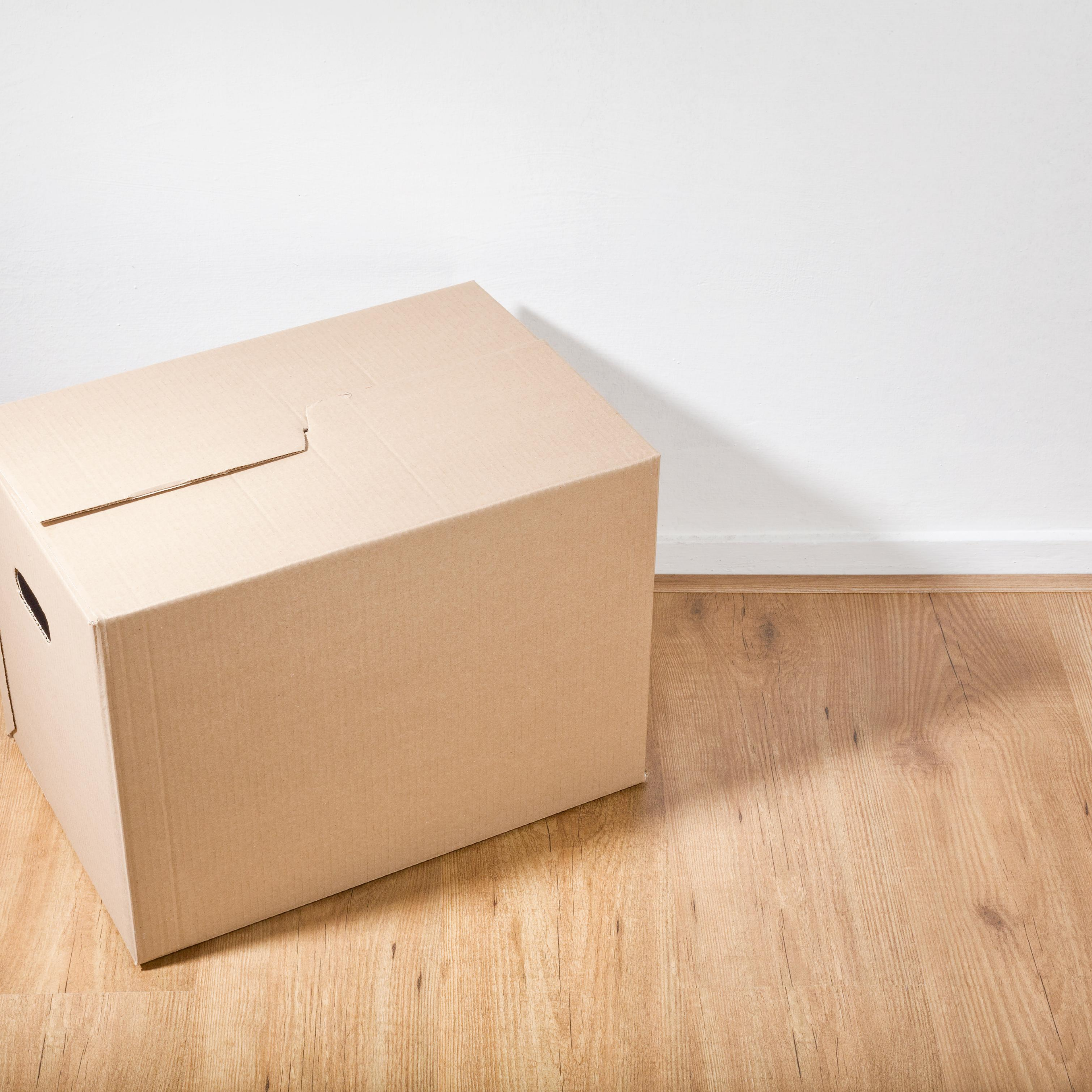 """Moving box on wooden floor with white wall in background, represents """"Match With a Roommate"""" program"""