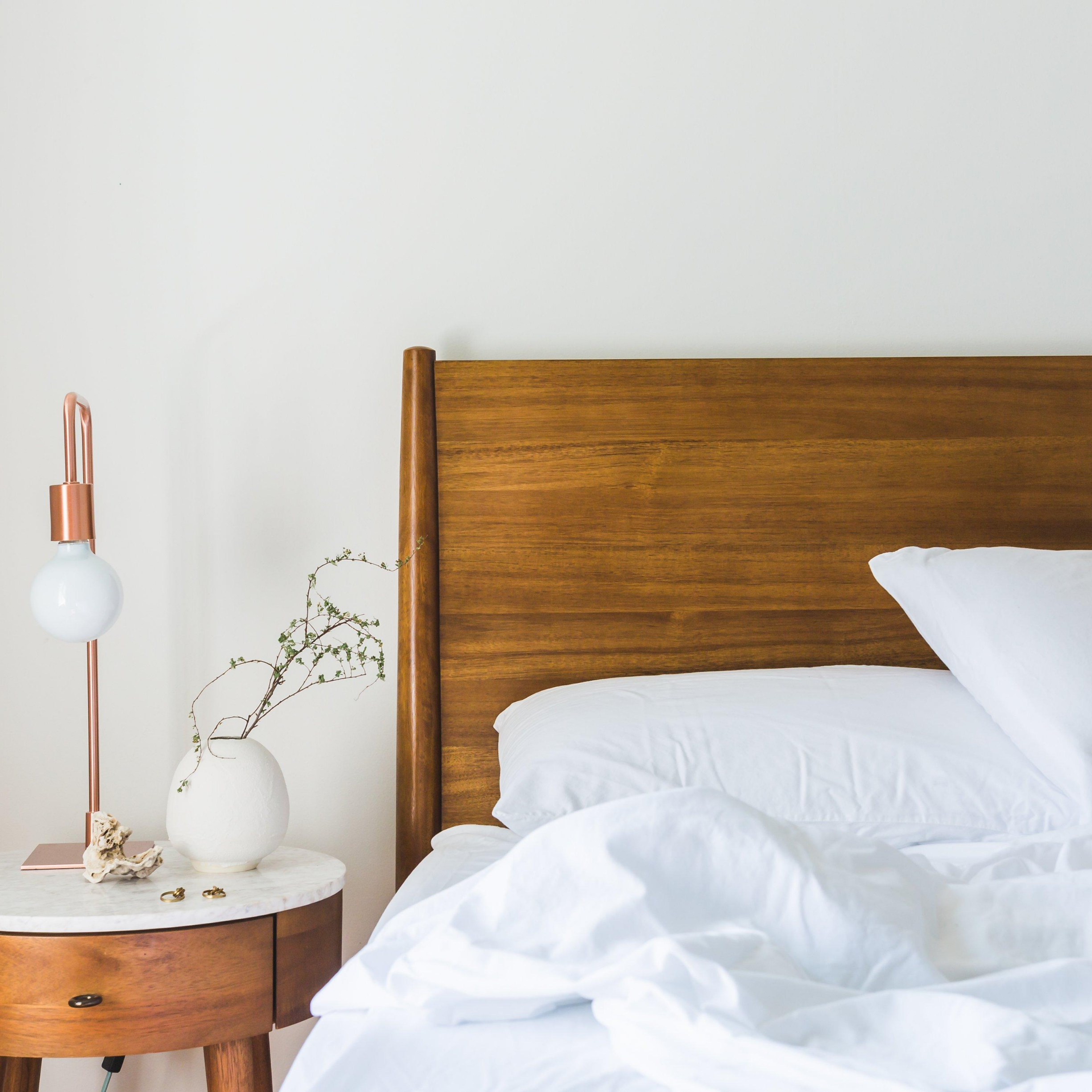 """Bed with wood headboard, white sheets, wooden night stand with white vase and lamp against a white wall, represents """"Need Some Sleep Advice?"""" program"""