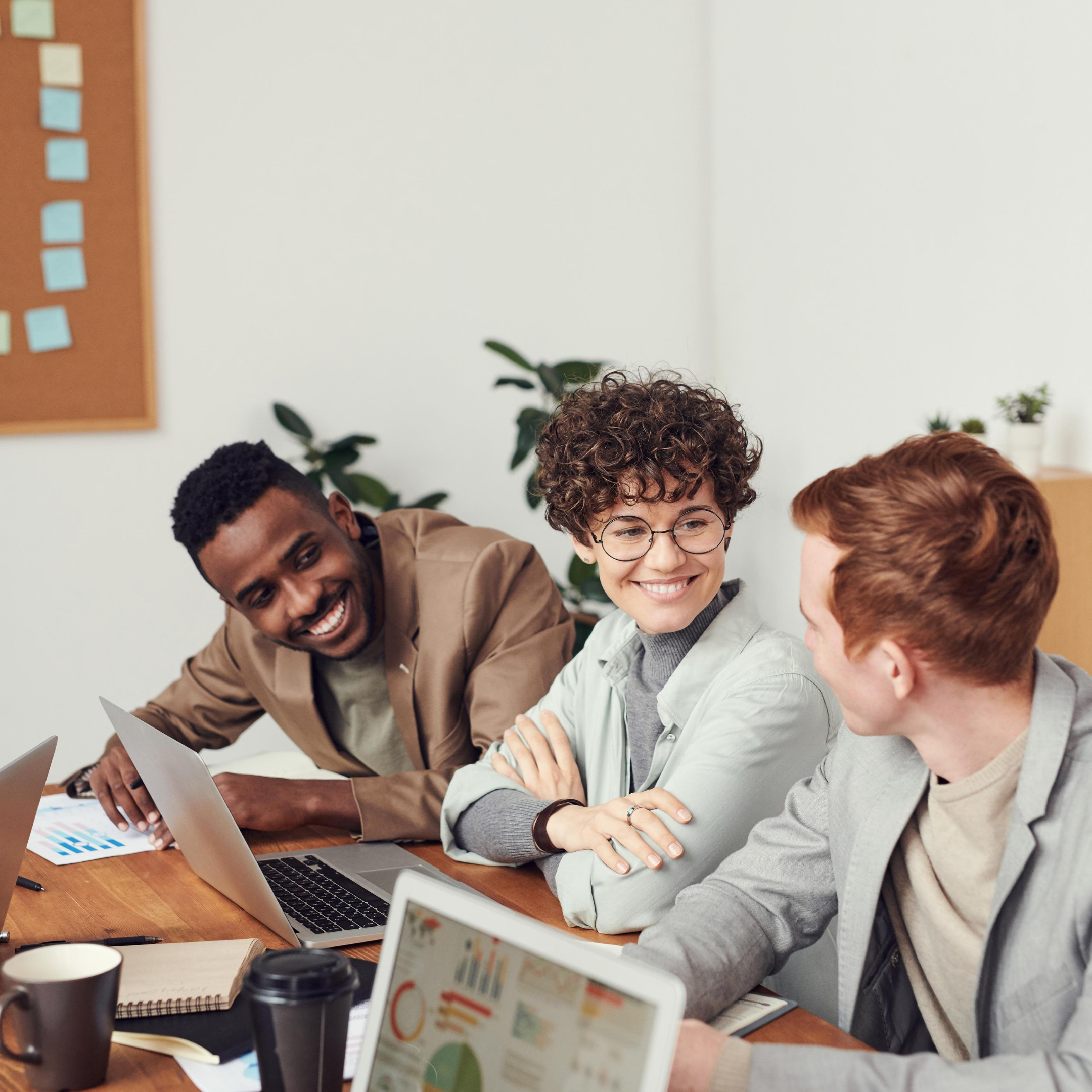 """Three people smiling at wooden desk with notebooks, open computers and coffee with white background and corkboard and plants all in professional attire, represents """"Identify A Study Group"""" program"""