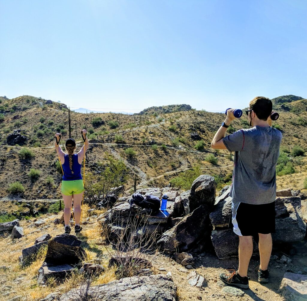Couple performing shoulder press surrounded by desert hills. Personal wellness, Total Body Conditioning on the Mountian.