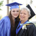 GCCA grad and faculty member pose for picture at graduation ceremony