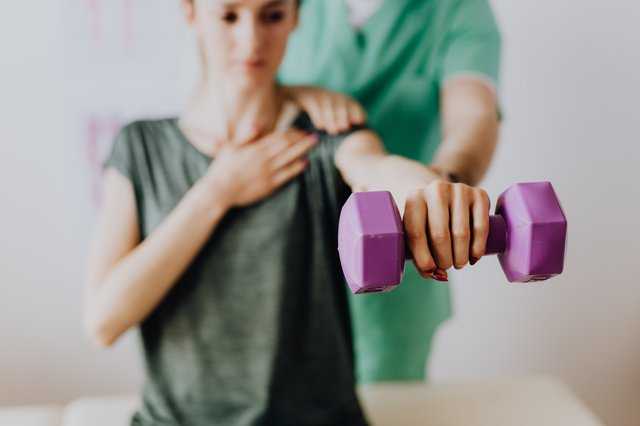 crop-anonymous-osteopath-assisting-patient-with-dumbbell-in-4506078