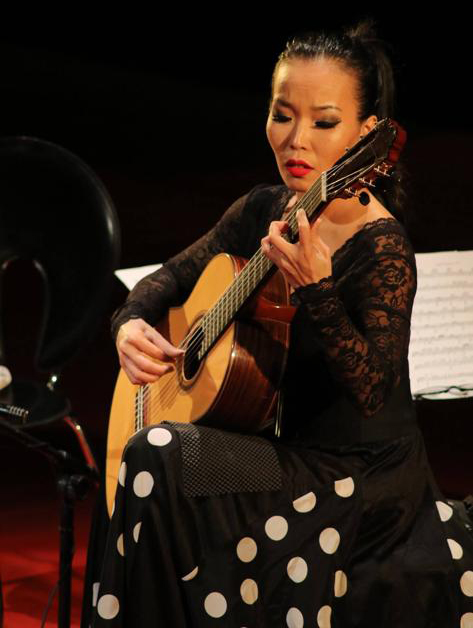 Photo of Thu Le playing classical guitar