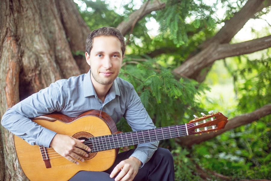 Photo of Jerome Mouffe posing with a classical guitar under a tree