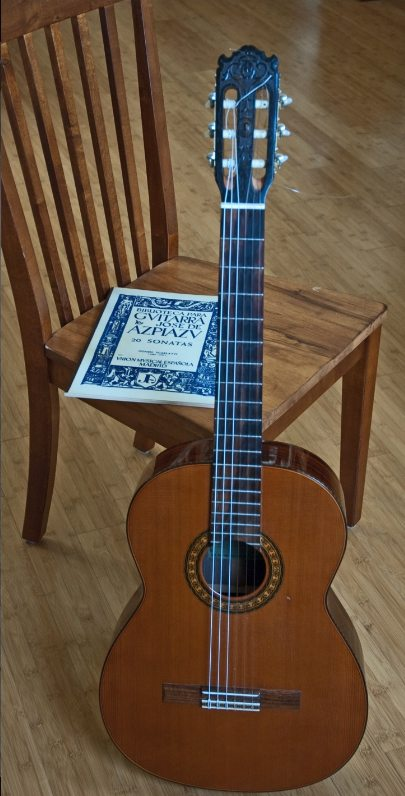 Photo of a classical guitar leaning against a chair with sheet music