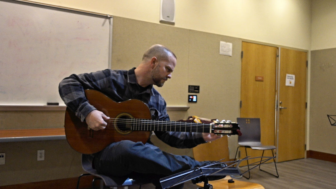 Photo of Mark Aitken, tuning guitar at Open Mic before performing