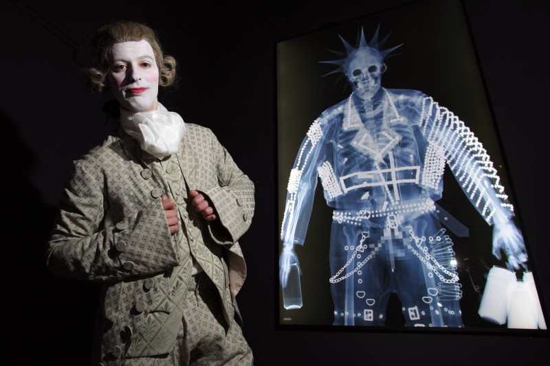'Shaping The Body' Exhibition at The York Castle Museum. A major new exhibition exploring the way fashion, food and fitness have shaped the body over the last 400 years, opens at The York Castle Museum in York, on Friday 25th March 2016. The exhibition features an iron corset, crotchless pantaloons from the time of Jane Austen, bum rolls and a killer dress (made from arsenic), and a diminutive dress worn by Queen Victoria, and traces the changing fashion trends and body shapes from the waist clinching Tudor corset through to Punk Rock and to the extremes of transgender men and women to those with piercings and tattoos. The Exhibition 'Shaping the Body' opens to the public this Friday 25th March 2016. Seen here: Lee Clark from The York Museums Trust dressed in a Georgian Macaroni Suit, in the shadow of an X-ray of a Punk with all his piercings..!!!