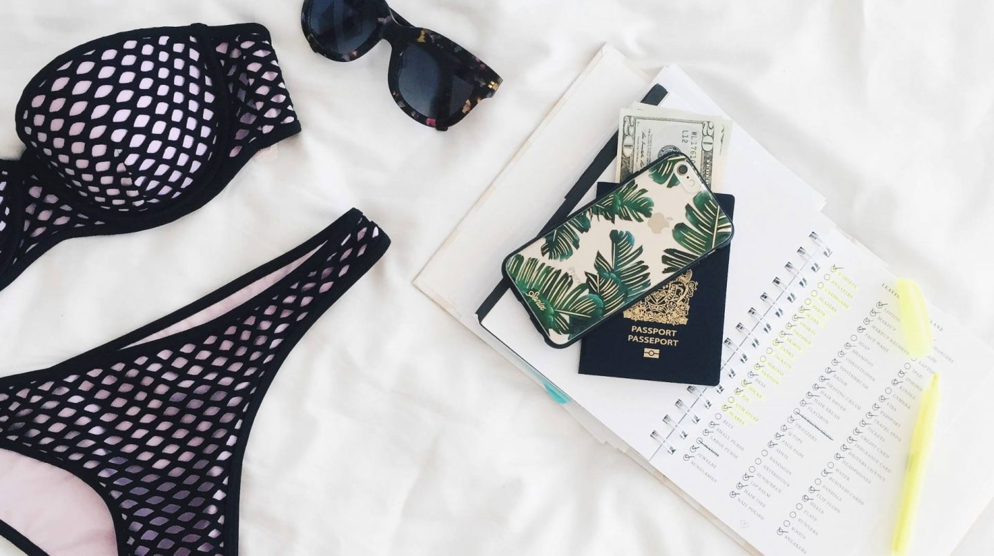 swimwear on a bed with diary, passport, sunglasses and iPhone