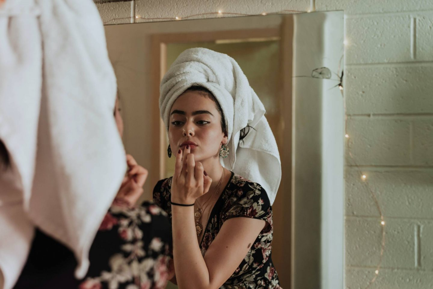 A woman with a towel looking in the mirror