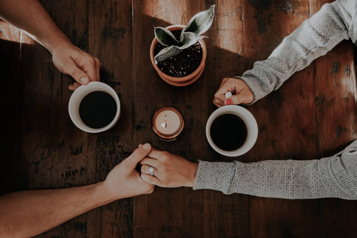 Couple with coffee cups holding hands