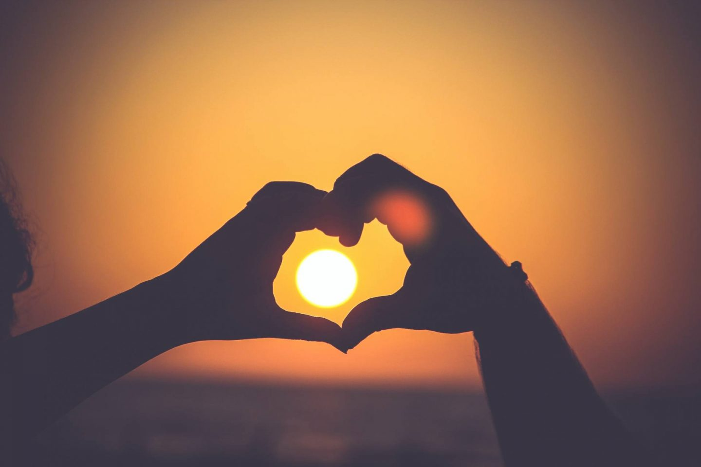 """wo people hold their hands up in front of a sunset, making a """"heart"""" shape."""