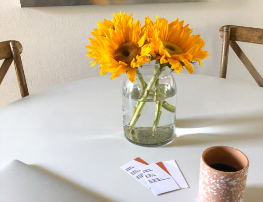 white table with sunflowers in glass vase, cup of coffee and a macbook air laptop showcasing business cards