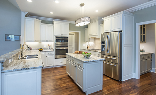 Kitchen with stainless steel fixtures and white cabinets