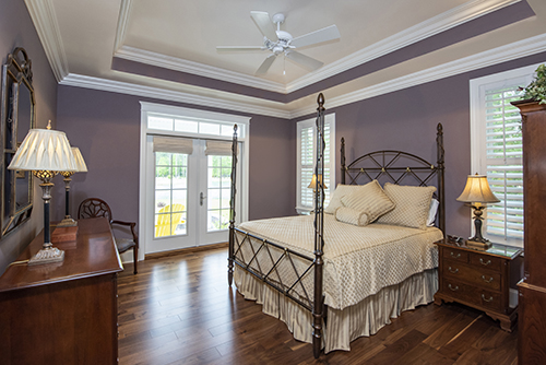 Large Bedroom with custom tray ceiling and hard wood floors
