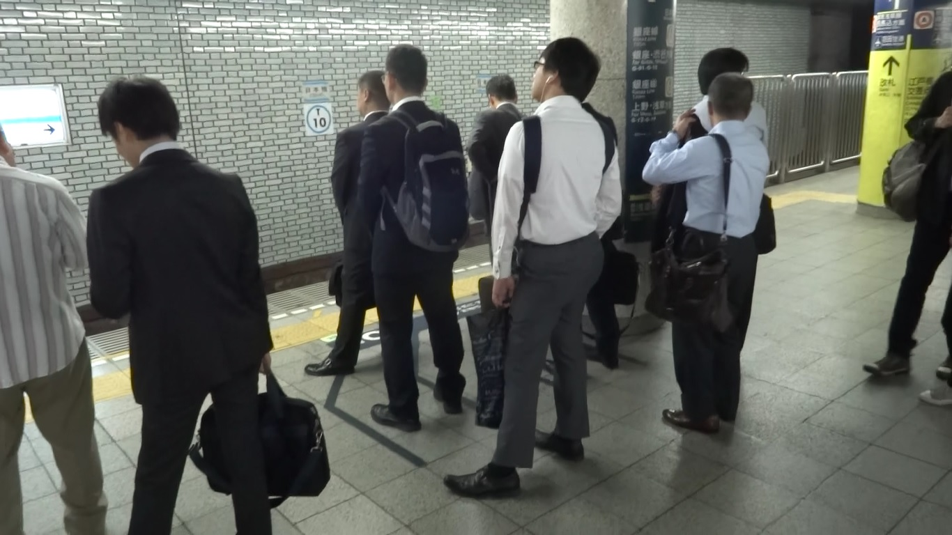 People waiting in line for the next metro train.