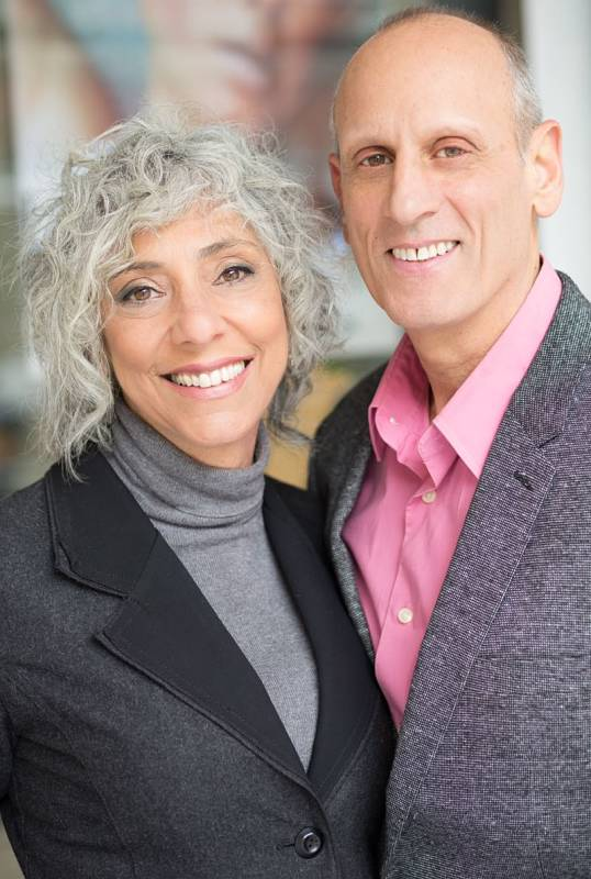 woman in curly gray hair next to smiling man in pink shirt